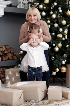 Happy senior woman closing eyes to her grandchildren, pretty little sibling, to give a Christmas gift before New Year Tree, merry Christmas concept, happy family, lifestyle indoor, studio shot