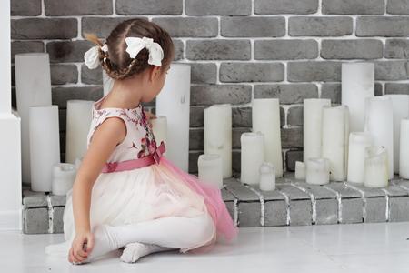 Vrij kleine echte damezitting vóór witte decoratieve open haard met kaarsen, het concept van de de wintervakantie, gelukkige familie, levensstijl binnen, studioschot