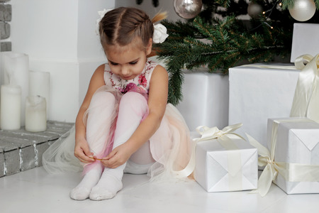 Portrait of thoughtful little girl sitting under decorated New Year Tree near packed present, merry Christmas and winter holiday concept, happy family, lifestyle indoor, studio shot