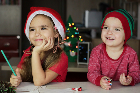 Cute small siblings, boy and girl in red hats, writing a letter to Santa Claus and thinking about his presents for them, Christmas background, winter holiday concept