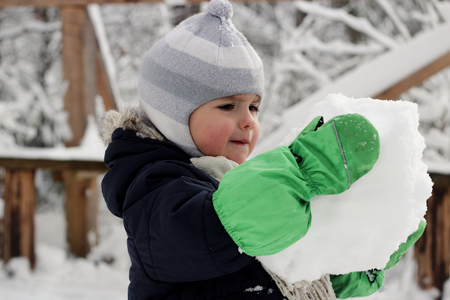 Serious toddler boy in warm coat and green mitts holding a huge snowball and having fun in the winter forest, happy winter weekend, outdoor portrait