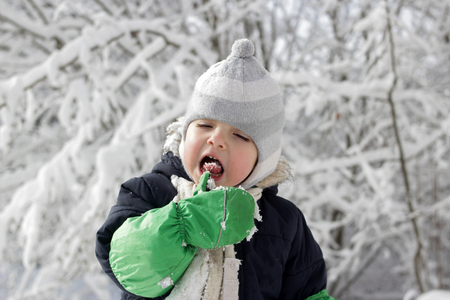 Little toddler boy in warm coat and knitted hat having fun in the winter forest and trying to catch snowflakes with his mouth, outdoor portrait