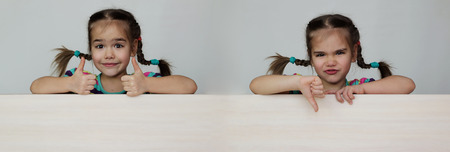 Double photo of cute 5 years old girl with funny pigtails showing like and dislike gestures with thumb up and down on white board, space for copy, advertising and announcement concept, studio shot over white background Stock Photo