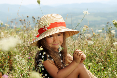 Pretty little girl in an elegant dress and straw hat relaxing on the top of the mountains, summer, vacation, travel concept, she gathers flowers, outdoor portrait