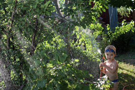 A happy little boy in the watersport goggles with a pistol in his hands watering the garden in the summer cottage during summer vacation, happy family summertime concept, outdoor lifestyle