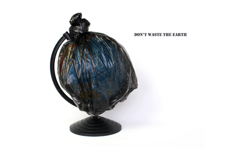 A globe of the earth in a plastic black bag like trash over white background, the concept of ecology problem and World Environment Day. Photo with message for social advertising, place for inscription Фото со стока