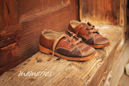 Cute baby retro shoes over wooden doorstep of old village house, retro country style, childhood and recollections Stock fotó