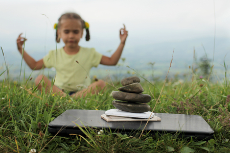 Cute 5-6 year girl meditating in the mountains. Stack of zen stones and digital gadget, laptop and mobile phones, on the green grass. Relax and self-development concept, summer outdoor 版權商用圖片