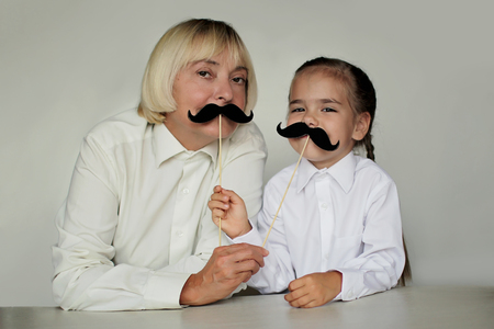 A cute little girl and her grandmother holding a fake felt moustaches in a stick in front of their faces, happy father day and men health concept Banco de Imagens