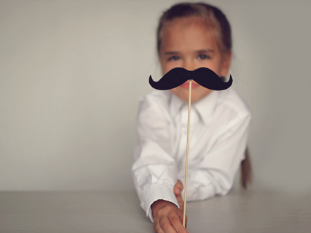 A cute little girl holding a fake felt moustache in a stick in front of her face, happy father day and men health concept Foto de archivo - 107981655