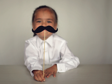 A cute little girl holding a fake felt moustache in a stick in front of her face, happy father day and men health concept