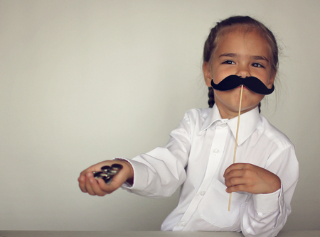 A cute little girl holding a fake felt moustache in a stick in front of her face and coins in her hand over white background, happy father day and men health concept