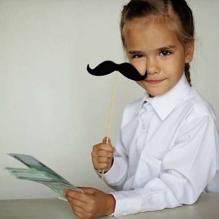 A cute little girl holding a fake felt moustache in a stick in front of her face and paper money in her hand over white background, happy father day and men health concept Foto de archivo - 107981660