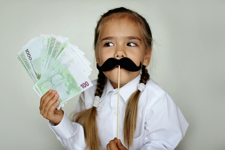 A cute little girl holding a fake felt moustache in a stick in front of her face and paper money in her hand over white background, happy father day and men health concept Foto de archivo - 107981661