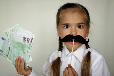 A cute little girl holding a fake felt moustache in a stick in front of her face and paper money in her hand over white background, happy father day and men health concept Foto de archivo - 107981663
