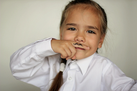 A cute little girl holding a finger in front of her face with drawn fake moustache on it, happy father day and men health concept