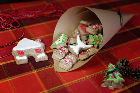 Festive Christmas paper bag with sweet cookies, house, snowflakes and pigs, new year symbol, classical red and brown Christmas color, winter holidays concept Stok Fotoğraf