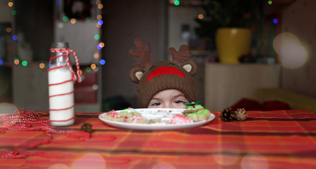 Cute toddler boy in the hat of reindeer stretching his hand to festive Christmas plate with sweet cookies, classical red and brown Christmas color, winter holidays concept