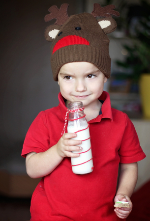 Cute toddler boy in the hat of reindeer drinking milk and eating a cookie from the festive plate with Christmas sweets, classical red and brown Christmas color, winter holidays concept Stok Fotoğraf