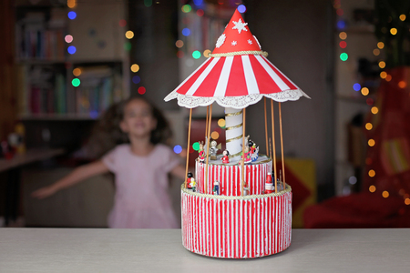 Cute preschool girl looking with admiration on the Christmas red merry-go-round carousel, crafted paper toy over blurred background, winter holidays concept Stok Fotoğraf