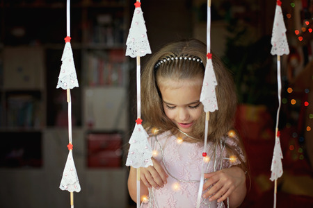 Cute preschool girl in beautiful gala dress over crafted paper trees garland, winter holidays concept