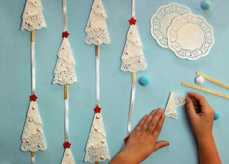 Christmas crafted garland with trees from paper serviettes lays on the blue color background, original craft and diy concept for kid and kindergarten Stok Fotoğraf