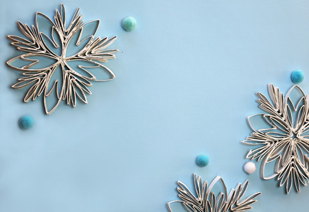 Christmas crafted snowflakes with paper toilette roll lays on the blue color background, original craft and diy concept for kid and kindergarten