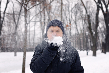 Middle aged man in black coat blowing on the snow in his arms, winter outdor, merry season activities