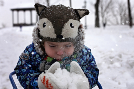 Happy toddler boy in warm coat and funny hat blowing on the snow in his arms, winter outdoor, merry season activities