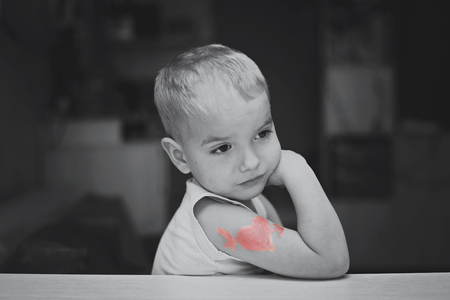 Little boy with heart symbol tattoo thinking thoughtfully, he falls in love unhappy, romantic and love concept, Valentine Day greeting, black and white