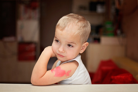 Little boy with heart symbol tattoo thinking thoughtfully, he falls in love unhappy, romantic and love concept, Valentine Day greeting