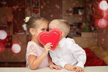 Little boy in white shirt and soft pink bow-tie and beautiful little princess wearing soft pink dress kissing behind a red heart, they fall in love, romantic and love concept, Valentine Day greeting Stok Fotoğraf