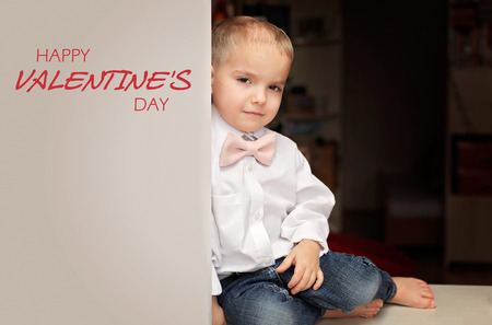 Little boy in white shirt and soft pink bow-tie sitting on the desk and looking confidently, he falls in love, romantic and love concept, Valentine Day greeting, place for text