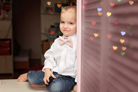 Little boy in white shirt and soft pink bow-tie sitting on the desk and looking confidently, he falls in love, romantic and love concept, Valentine Day greeting