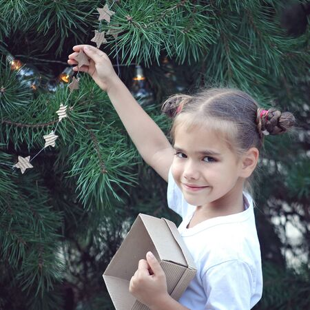 Cute school girl holding crafted Christmas garland made from used paper box, zero waste lifestyle, reuse and ecological decoration