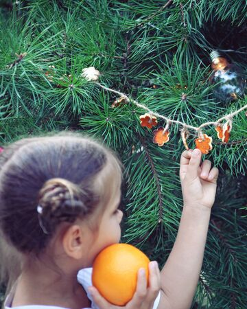 Cute school girl holding crafted Christmas garland made from the skin of oranges, zero waste lifestyle, reuse and ecological decoration
