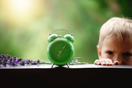 Toddler boy switching off a green alarm clock with lavender flowers on the wooden table of a veranda over blurred green background, summer morning outdoor, concept