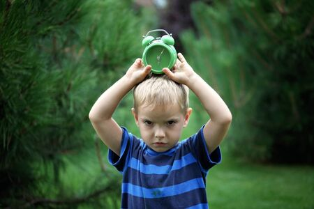 Sleepy toddler boy holding a green alarm clock on his head over blurred green background, summer morning outdoor, concept