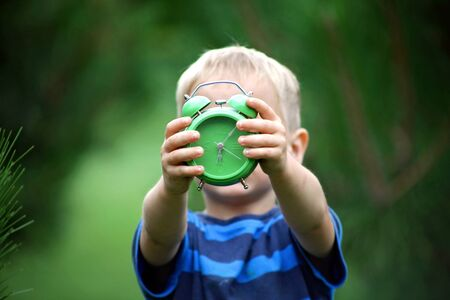 Sleepy toddler boy holding a green alarm clock before his face over blurred green background, summer morning outdoor, concept
