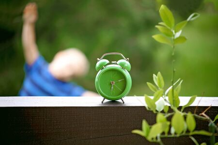 Close up of a green alarm clock and toddler boy doing his morning exercises over blurred green background, summer morning outdoor, healthy lifestyle