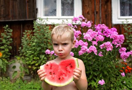 Happy 4-5 years old preschool boy eating a fresh just harvested watermelon and smiling in camera on a background of a countryside farm, summertime in the countryside, outside portrait