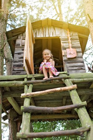 Happy cute kid playing in the treehouse in summer, happy summertime in countryside, ecological playground