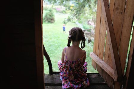 Cute kid sitting alone in the treehouse in summer, summertime in countryside, ecological playground, back view