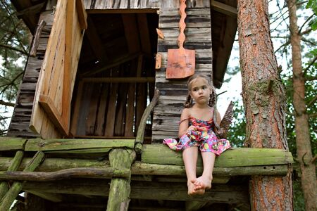 Cute kid sitting alone in the treehouse in summer, summertime in countryside, ecological playground