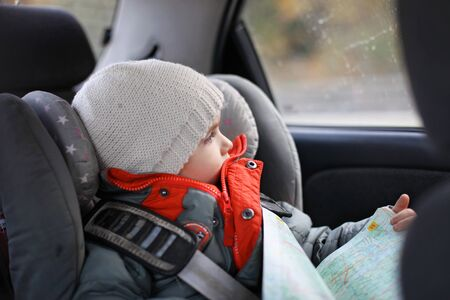 Adorable little boy exploring a map during his road trip on vacations with his parents. Happy family vacations and safety on the road.