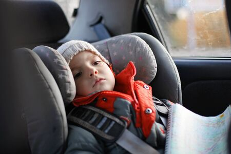 Adorable little boy exploring a map during his road trip on vacations with his parents. Happy family vacations and safety on the road. Stockfoto