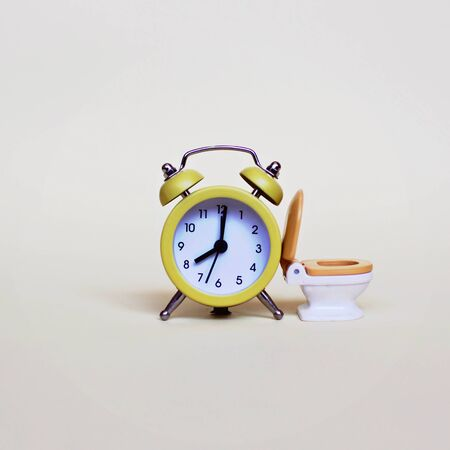 Yellow alarm clock and white toilette bowl over light background, healthcare and wasting time concept