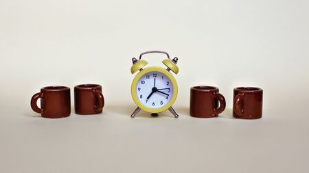 Yellow alarm clock and several tiny brown cups with coffee over light background, food and drink, morning and active working day concept, banner format Stock Photo