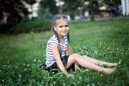 Cute 5-6 years old sitting on the green grass and listening the music with earphones, she is cute and happy, close-up candid portrait, summer outdoor