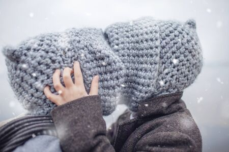 Little pretty girl in knitted grey hat hugging her frozen smaller brother during snowfall in winter, white cold weather, winter outside lifestyle close-up portrait